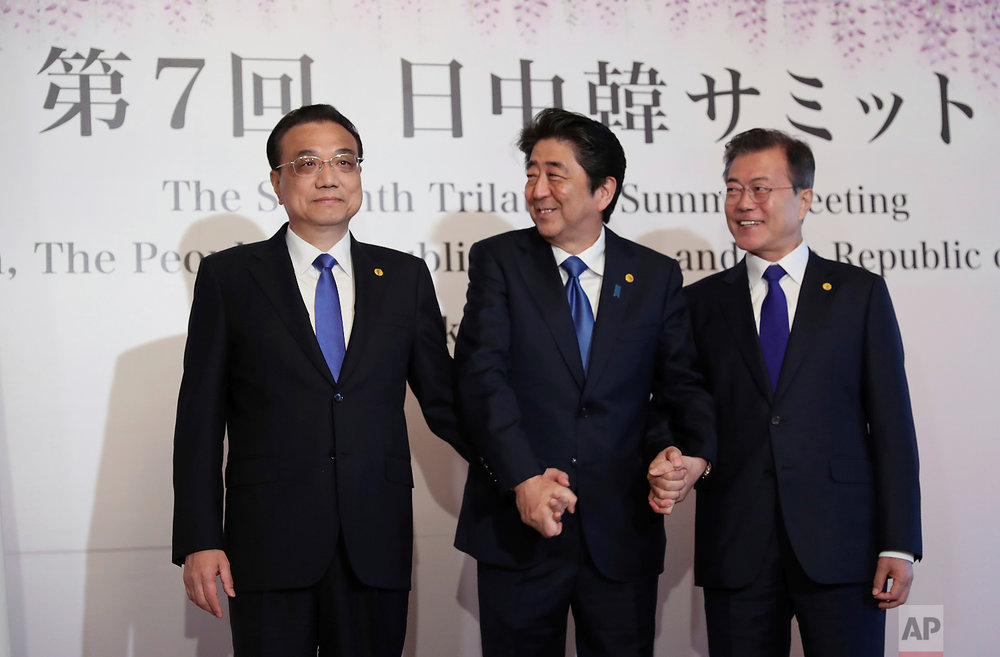 Chinese Premier Li Keqiang, left, Japanese Prime Minister Shinzo Abe, center, and South Korean President Moon Jae-in pose for photographers prior to their summit meeting in Tokyo on May 9, 2018. (AP Photo/Eugene Hoshiko)