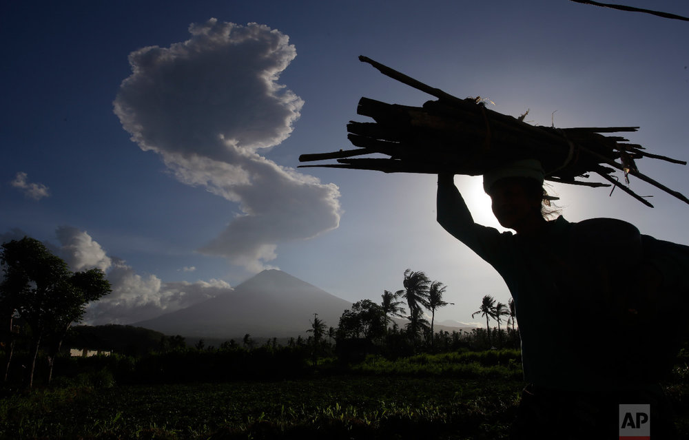 A woman carries wood past as the Mount Agung spews ash and smoke in the background in Karangasem, Bali, Indonesia on July 5, 2018. (AP Photo/Firdia Lisnawati)