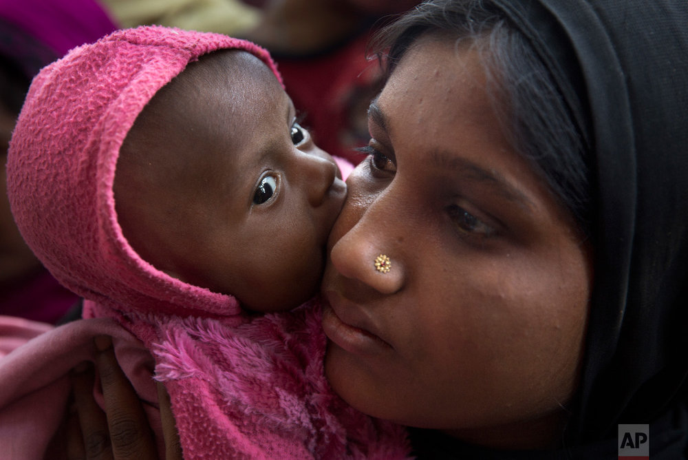 A newly arrived Rohingya refugee child licks the cheek of her mother Azida Khatoon, 20, as they wait in a food distribution line in the Kutupalong refugee camp near Cox's Bazar, Bangladesh on Jan. 27, 2018. (AP Photo/Manish Swarup)