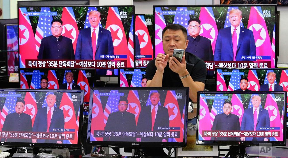 TV screens show U.S. President Donald Trump, right, meeting with North Korean leader Kim Jong Un in Singapore, during a news program at Yongsan Electronic store in Seoul, South Korea on June 12, 2018. (AP Photo/Ahn Young-joon)