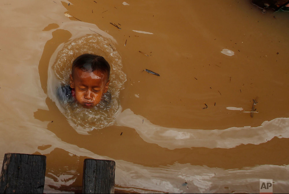 A boy swims during a flood season in the floating village on the Mekong river bank on the outskirts of Phnom Penh, Cambodia, on Aug. 11, 2018. (AP Photo/Heng Sinith)