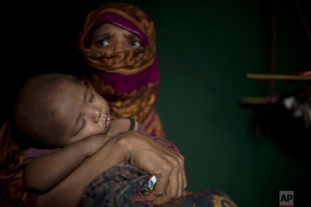 """S"" holds her baby boy as she sits in her shelter in Balukhali refugee camp in Bangladesh on June 25, 2018. ""S,"" a widow, was so worried about her neighbors discovering her pregnancy that she suffered silently through labor in her shelter, stuffing a scarf in her mouth to swallow her screams. (AP Photo/Wong Maye-E)"