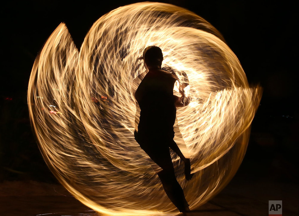 A Filipino fire dancer performs for the last time a day before the government implements the temporary closure of the country's most famous beach resort island of Boracay, in central Aklan province, Philippines, on Wednesday, April 25, 2018. Tourists are spending their final hours on Boracay, enjoying the Philippine island's famed white-sand beaches before it closes for up to six months to recover from overcrowding and development. (AP Photo/Aaron Favila)
