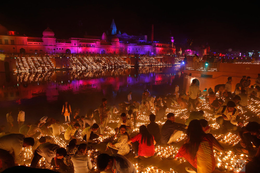 Devotees light earthen lamps on the banks of the River Sarayu as part of Diwali celebrations in Ayodhya, India, India, Tuesday, Nov. 6, 2018. The north Indian City of Ayodhya made an attempt to break the Guinness Book of World record when several earthen lamps were lit at the banks of river Saryu on the occasion of Diwali – the festival of light. (AP Photo/Rajesh Kumar Singh)