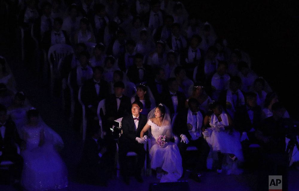 A couple watches a screen during a mass wedding ceremony at the Cheong Shim Peace World Center in Gapyeong, South Korea Monday, Aug. 27, 2018. South Korean and foreign couples exchanged or reaffirmed marriage vows in the Unification Church's mass wedding arranged by Hak Ja Han Moon, wife of the late Rev. Sun Myung Moon, the controversial founder of the Unification Church. (AP Photo/Ahn Young-joon)