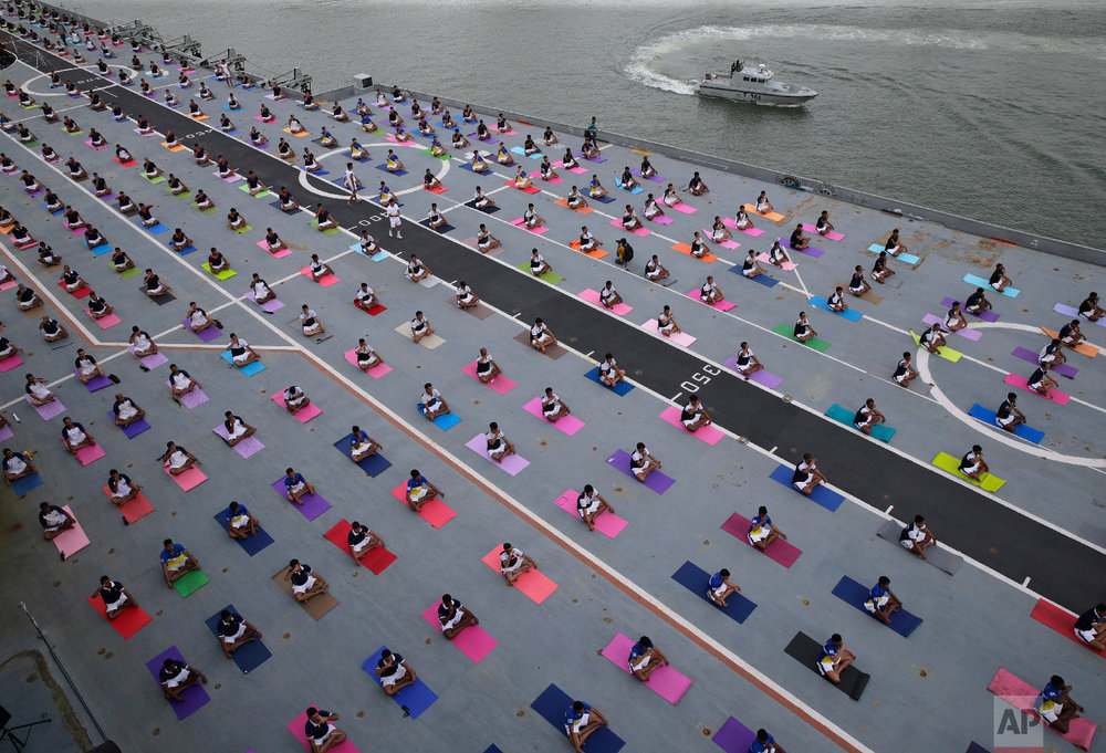 Indian defense personnel perform yoga on the deck of Indian naval aircraft carrier Viraat as they mark International Yoga Day in Mumbai, India Thursday, June 21, 2018. Millions of yoga enthusiasts across the world Thursday took part in mass yoga events to mark International Yoga Day. (AP Photo/Rafiq Maqbool)