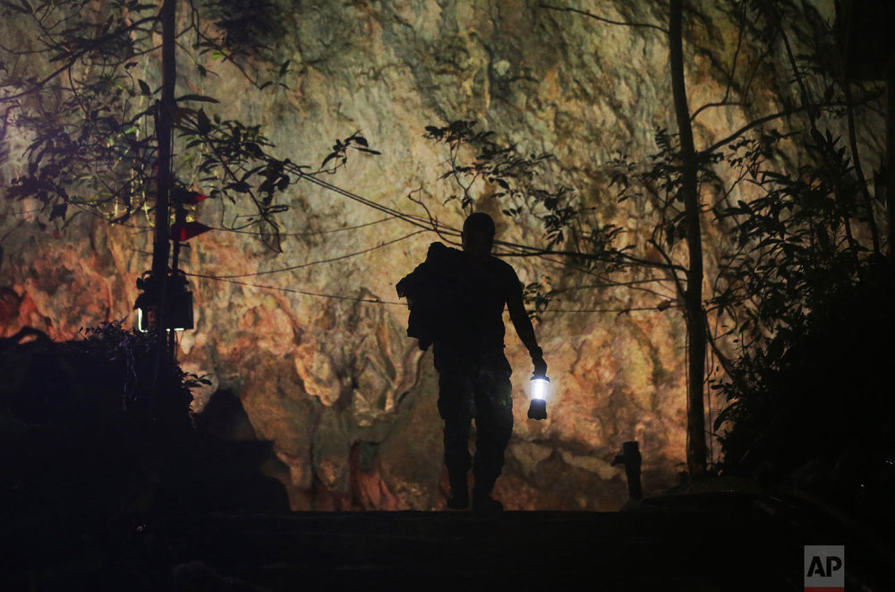 A rescuer makes his way down the entrance to a cave complex where 12 boys and their soccer coach went missing in Mae Sai, Chiang Rai province, northern Thailand Wednesday, July 4, 2018. (AP Photo/Sakchai Lalit)