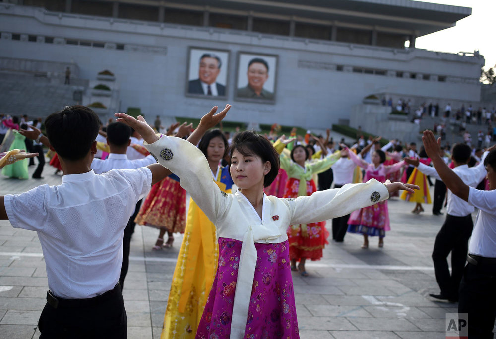 "North Koreans take part in a mass dance during the commemoration of the 65th anniversary of the end of the Korean War, which the country celebrates as the day of ""victory in the fatherland liberation war"", at Kim Il Sung Square in Pyongyang, North Korea, Friday, July 27, 2018. (AP Photo/Dita Alangkara)"