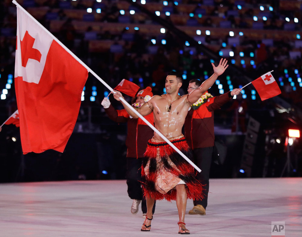 Pita Taufatofua carries the flag of Tonga during the opening ceremony of the 2018 Winter Olympics in Pyeongchang, South Korea, Friday, Feb. 9, 2018. (AP Photo/Petr David Josek)