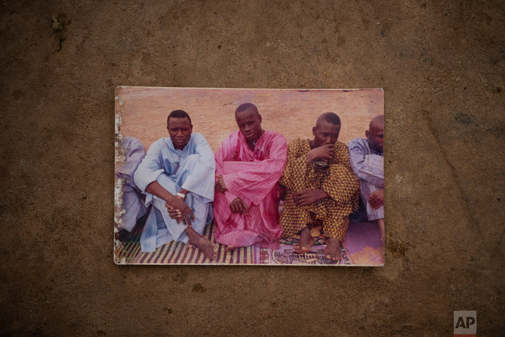 Tidiane Fofana, center, is pictured sitting with friends, in Goudiry, Senegal. Tidiane was one of 18 children; though the only one who noticed when his aging father or widowed aunt needed help. It was Tidiane who wanted to reach Europe to earn enough so that his father would never again have to ride his bicycle to the family's fields to work. (AP Photo/Felipe Dana)