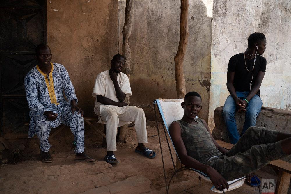People sit outside in the shade in a village on Nov. 24, 2018, near Goudiry, Senegal. (AP Photo/Felipe Dana)