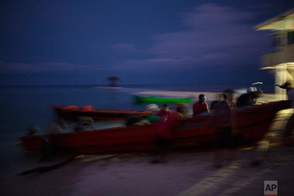 In this Sept. 10, 2018 photo, Miskito fishermen push a boat onto the shore on Cay Savannah, Honduras, at the end of a fishing sea cucumber trip. (AP Photo/Rodrigo Abd)