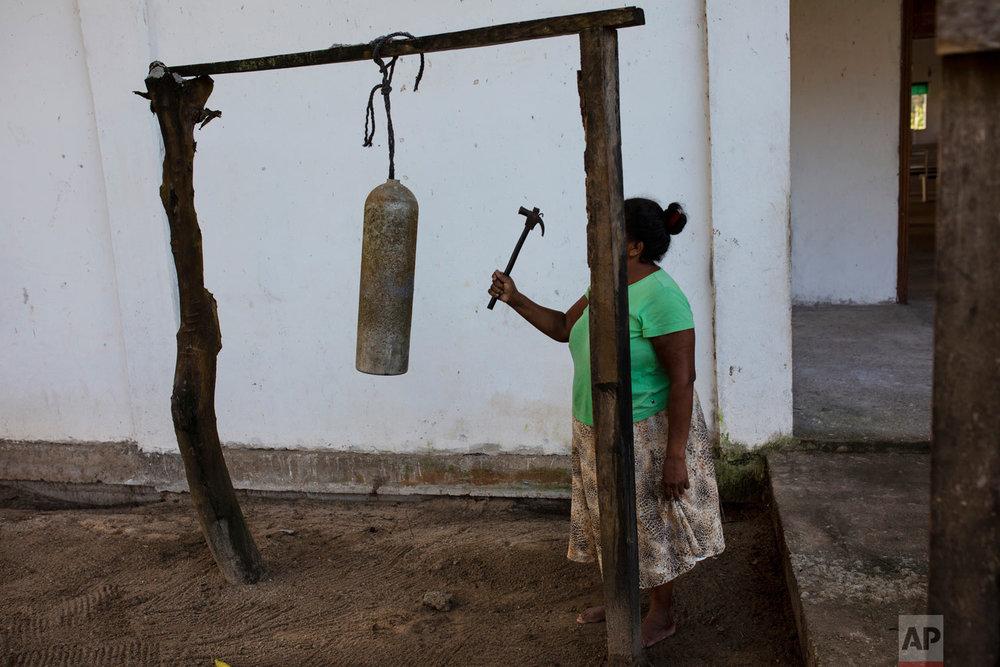In this Feb. 11, 2018 photo, Elvira Mendoza Espinosa, hits a diving tank with a hammer announcing the start of the morning Mass, outside the Moravian church in Kaukira, Honduras. (AP Photo/Rodrigo Abd)