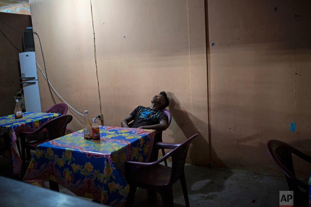 In this Feb. 9, 2018 photo, a man takes a nap inside a makeshift restaurant in Puerto Lempira, Honduras. (AP Photo/Rodrigo Abd)