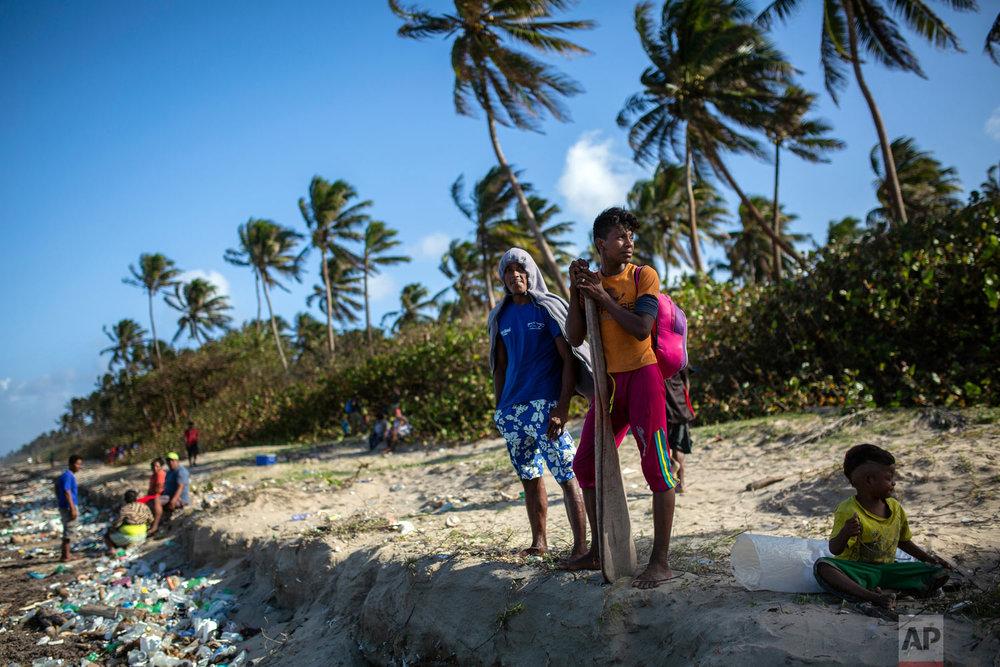 In this Feb. 10, 2018 photo, Miskito divers wait to board a boat for a two week fishing trip to harvest sea cucumbers, in Krata, Honduras. (AP Photo/Rodrigo Abd)