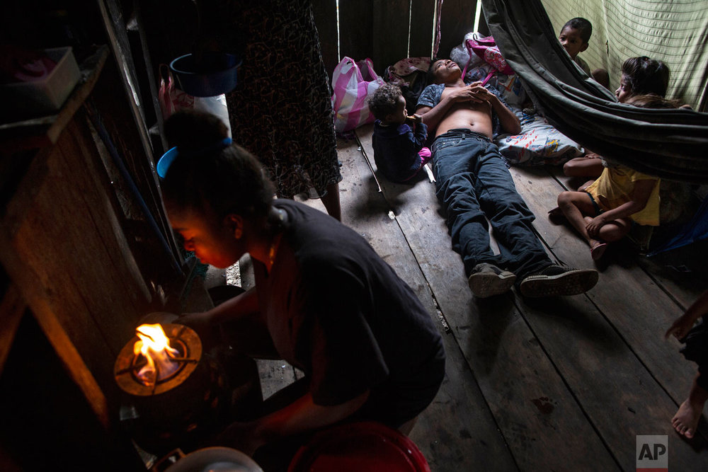 """In this Jan 31, 2018 photo, paralyzed by decompression sickness in 2017, lobster diver Charles """"Charly"""" Melendez, 28, stares at the ceiling lying on the floorboards of a rented room surrounded by his children, in Puerto Lempira, Honduras. (AP Photo/Rodrigo Abd)"""