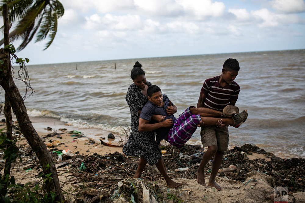 """In this Jan. 30, 2018 photo, Miskito diver Charles """"Charly"""" Melendez, 28, is carried by his 10-year-old son Jason and wife Kenia from their rented room along the shore in Puerto Lempira, Honduras, to a smoother ground for his wheelchair. (AP Photo/Rodrigo Abd)"""