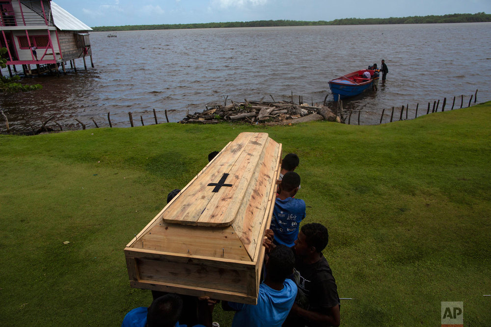 In this Sept. 2, 2018 photo, relatives and friends carry the coffin that contains the remains of Miskito diver Oscar Salomon Charly, 31, to a boat , to be transported to a nearby cemetery, in Cabo Gracias a Dios, Nicaragua.  (AP Photo/Rodrigo Abd)