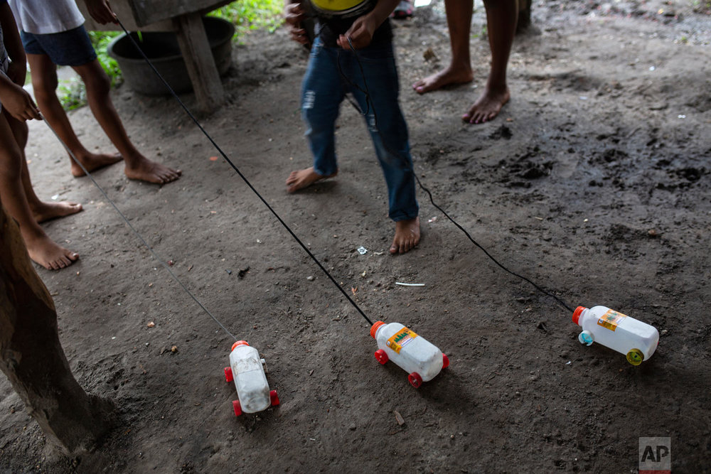 In this Feb. 6, 2018 photo, children hold onto to their toys made with recycled material, in Puerto Lempira, Honduras. A sign of the poverty, boys crafted toy trucks from plastic juice boxes with lids for wheels. For grown-ups, the only option they've found to deal with poverty is diving, no matter the risks. (AP Photo/Rodrigo Abd)