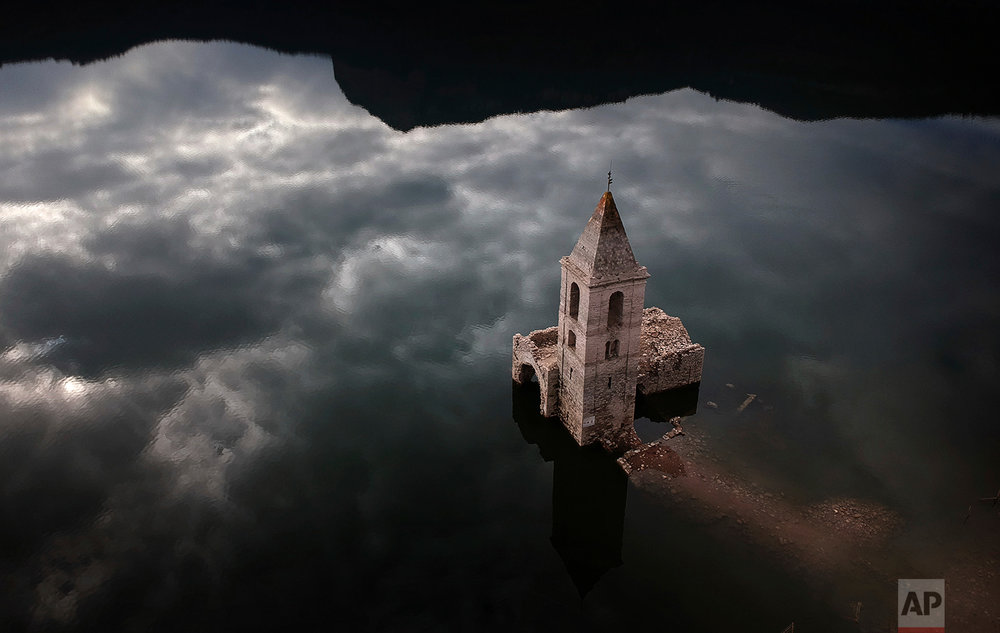 A church and remains of an ancient village which are usually covered by water are seen inside the reservoir of Sau, in Vilanova de Sau, Catalonia, Spain, Thursday, Jan 11, 2018. (AP Photo/Emilio Morenatti)