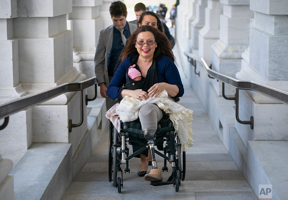 Sen. Tammy Duckworth, D-Ill., arrives at the Capitol for a close vote with her new daughter, Maile, bundled against the wind, in Washington, Thursday, April 19, 2018. In an historic change in Senate rules, the lawmakers decided to allow babies of members on the floor during votes. (AP Photo/J. Scott Applewhite)