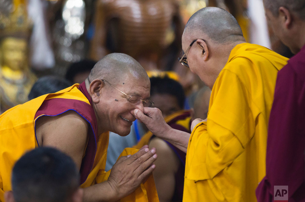 Tibetan spiritual leader the Dalai Lama playfully pinches the nose of a senior monk as he arrives to give a talk to Tibetan youth in Dharmsala, India, Thursday, June 7, 2018. (AP Photo/Ashwini Bhatia)