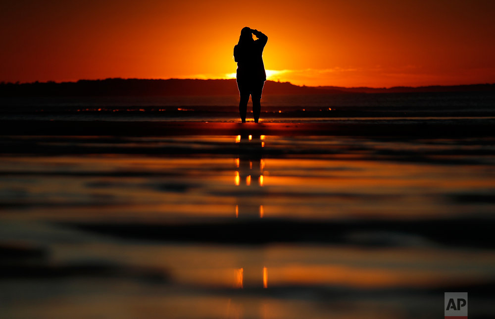 Consuello Jessop, of Providence, R.I., photographs the sunrise at Ocean Park, Thursday, July 12, 2018, in Old Orchard Beach, Maine. (AP Photo/Robert F. Bukaty)