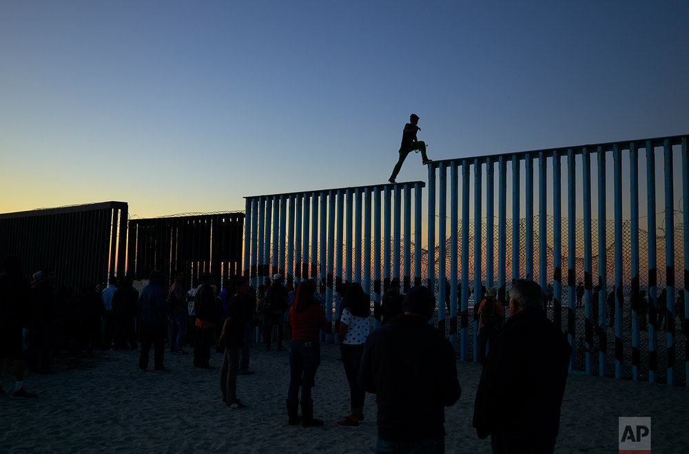 In this Nov. 14, 2018 picture, a man from Honduras walks along the top of the border structure separating Mexico and the United States, in Tijuana, Mexico. (AP Photo/Gregory Bull)