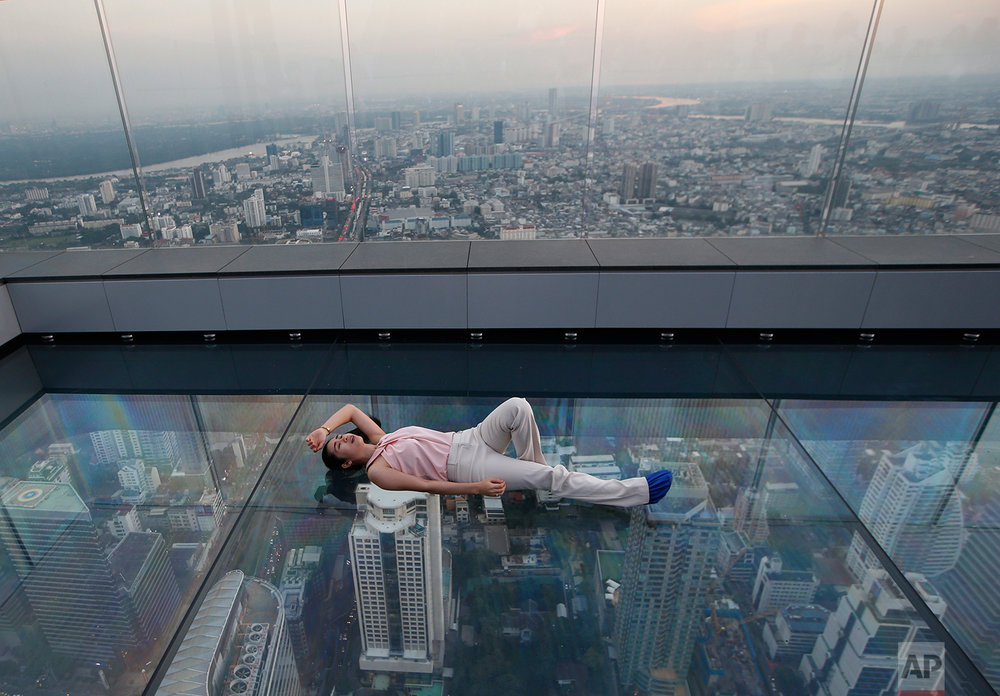 In this Nov. 21, 2018, photo, a woman lies on the glass bottom deck of the King Power Mahanakhon building high above Bangkok, Thailand. The King Power Mahanakhon building, currently Thailand's tallest at 314 meters (1,030 feet) with 78 floors, has a 360-degree view of Bangkok. (AP Photo/Sakchai Lalit, File)