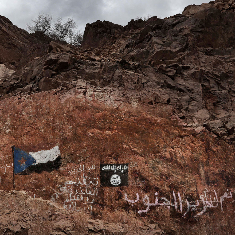 """This July 24, 2018 photo, shows the al-Qaida flag painted on rocks near the southern flag with Arabic that reads, """"Yes to liberating the south,"""" and """"the Organization of al-Qaida: Have a Safe Trip,"""" on a road in Shabwa, Yemen. (AP Photo/Nariman El-Mofty)"""