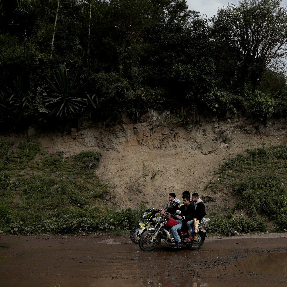 In this Aug. 3, 2018 photo, men chew qat, a narcotic leaf, as they make their way on a motorbike in Ibb, Yemen. (AP Photo/Nariman El-Mofty)