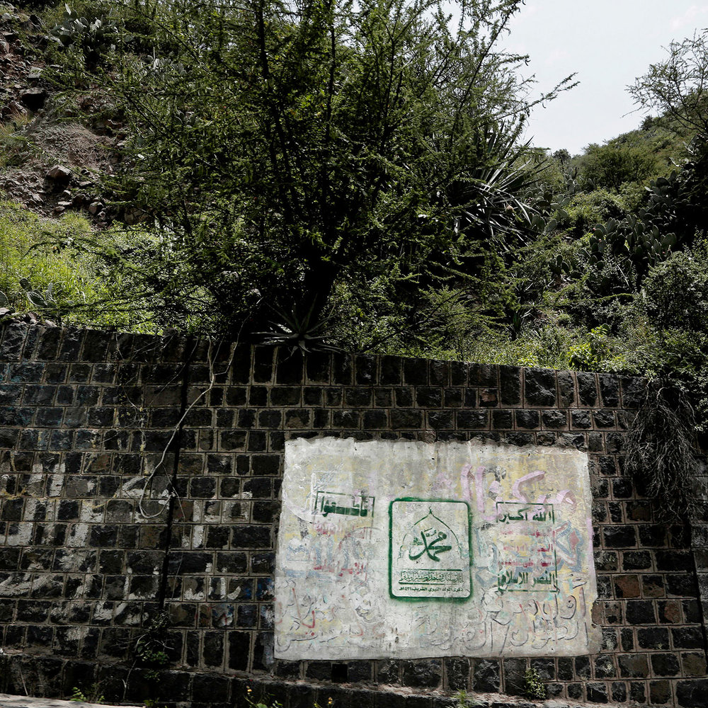 """This Aug. 3, 2018 photo, shows paint on a roadside with Arabic that reads, """"boycott America, Muhammad, God is great. Death to America. Death to Israel. Curse the Jews. Victory to Islam,"""" in Ibb, Yemen. (AP Photo/Nariman El-Mofty)"""