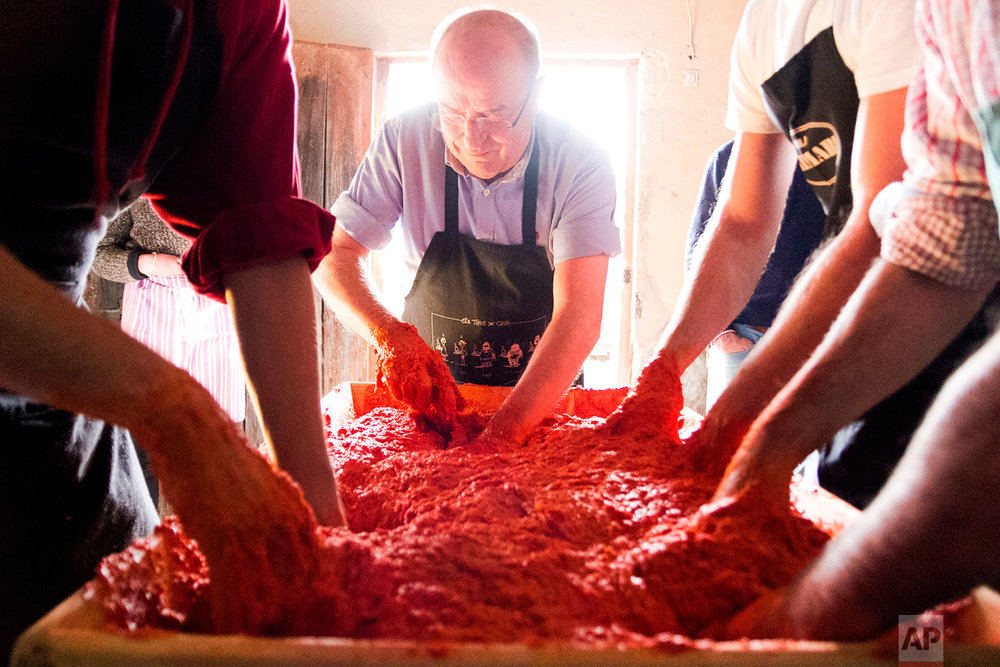 In this photo taken on Nov. 24, 2018, men mix the fat and selected shredded pork with other seasonings such as salt, paprika and black pepper for the production of sobrassada, a raw cured sausage, during the annual pig slaughter near Petra, some 60 kilometres from Palma, the capital of Mallorca, Spain. (AP Photo/Francisco Ubilla)