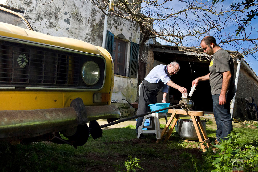 In this photo taken on Nov. 24, 2018, villagers use a meat grinder powered by an old Renault 4L engine, near Petra, some 60 kilometres from Palma, the capital of Mallorca, Spain. (AP Photo/Francisco Ubilla)