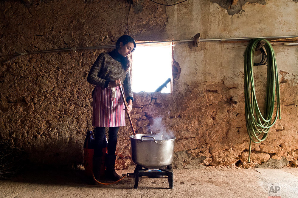 In this photo taken on Nov. 24, 2018, Laura, one of the women who has come to help with the slaughter, stirs the fat of the boiling pork for butter production during the annual pig slaughter near Petra, some 60 kilometres from Palma, the capital of Mallorca, Spain. (AP Photo/Francisco Ubilla)