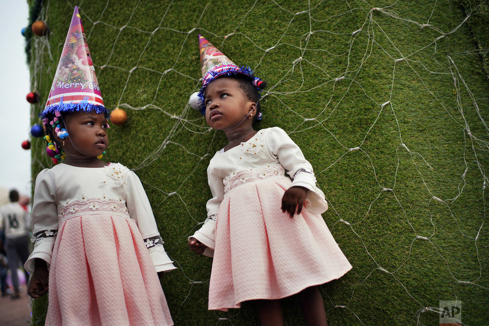 Twins pose for a photograph in Kinshasa, Congo, on Tuesday Dec. 25, 2018. People dress up and take to the parks on Christmas Day, this time five days before scheduled presidential and general elections. (AP Photo/Jerome Delay)