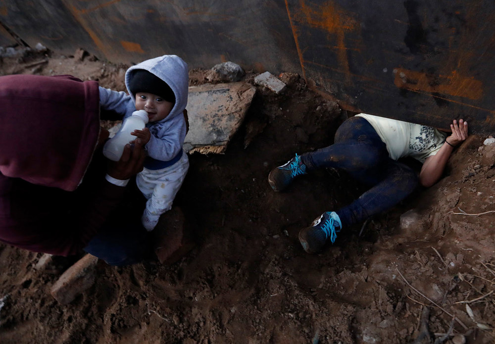Honduran migrant Joel Mendez, 22, feeds his eight-month-old son Daniel as his partner Yesenia Martinez, 24, crawls through a hole under the U.S. border wall, in Tijuana, Mexico, Friday, Dec. 7, 2018. (AP Photo/Rebecca Blackwell)