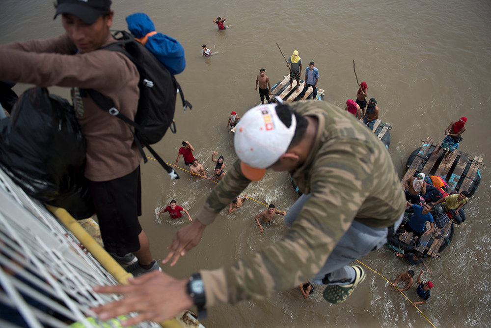 Migrants tired of waiting to cross into Mexico, jumped from a border bridge fence into the Suchiate River, in Tecun Uman, Guatemala, Friday, Oct. 19, 2018. (AP Photo/Oliver de Ros)