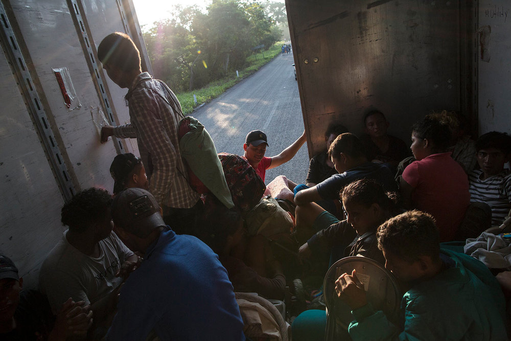 Migrants ride in the back of a truck, as a thousands-strong caravan of Central American migrants slowly makes its way toward the U.S. border, between Pijijiapan and Arriaga, Mexico, Friday, Oct. 26, 2018. (AP Photo/Rodrigo Abd)