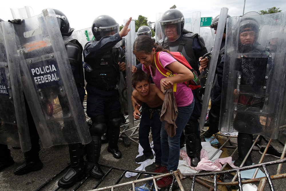 A Honduran migrant mother and child cower in fear as they are surrounded by Mexican Federal Police in riot gear, at the border crossing in Ciudad Hidalgo, Mexico, Friday, Oct. 19, 2018.  (AP Photo/Moises Castillo)