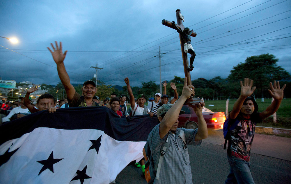 A Honduran migrant holds up a replica of the Black Christ of Esquipulas as a caravan of migrants making their way to the U.S. arrives to Esquipulas, Guatemala, Monday, Oct. 15, 2018. (AP Photo/Moises Castillo)
