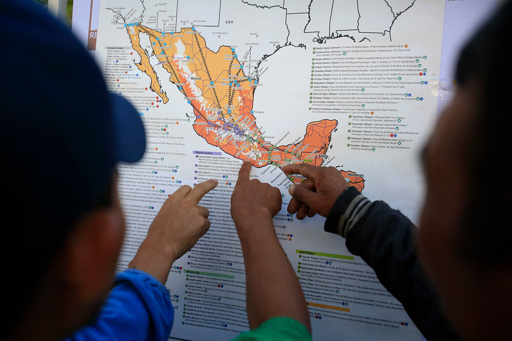 Migrants discuss their journey using a map posted inside the sports complex where thousands of migrants have been camped out for several days in Mexico City, Friday, Nov. 9, 2018. (AP Photo/Rebecca Blackwell)
