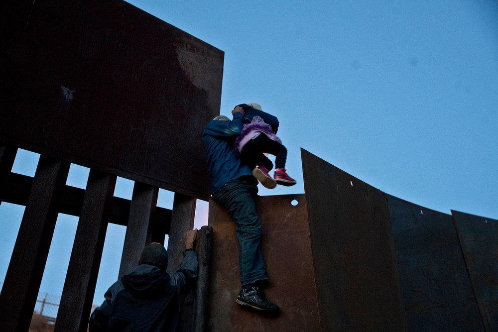 A Honduran migrant helps a young girl cross to the American side of the border wall, in Tijuana, Mexico, Sunday, Dec. 2, 2018. (AP Photo/Ramon Espinosa)