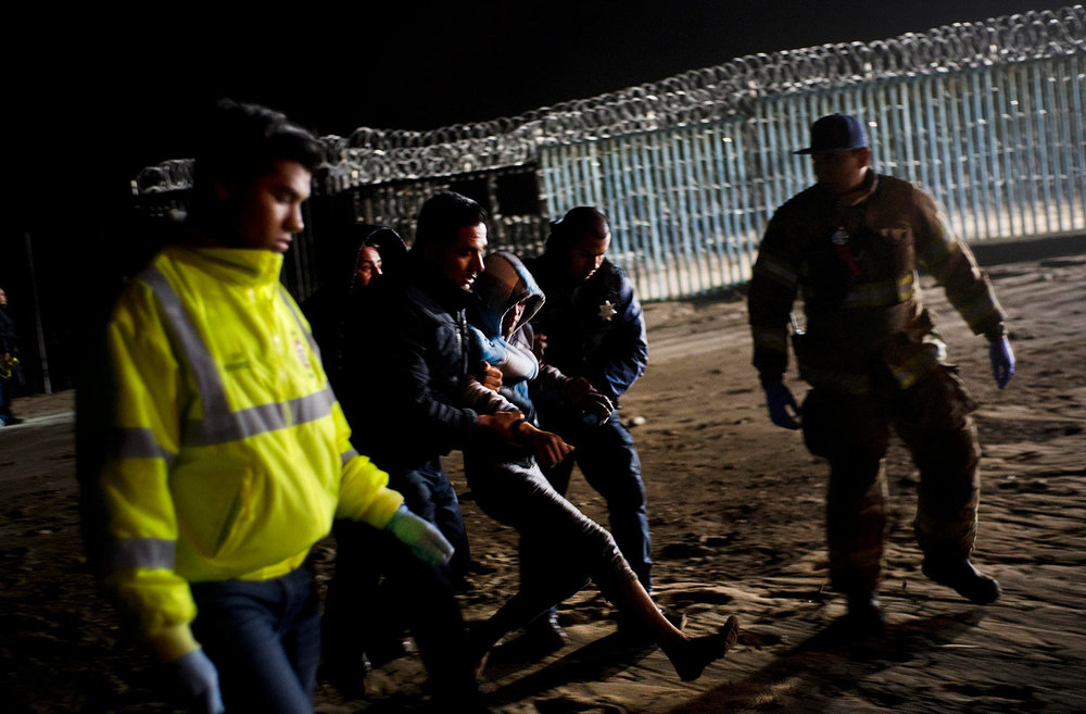 Authorities hold a Honduran migrant who was rescued after he tried to cross the US border by the sea in Tijuana beach, Mexico, Thursday, Nov. 29, 2018. (AP Photo/Ramon Espinosa)