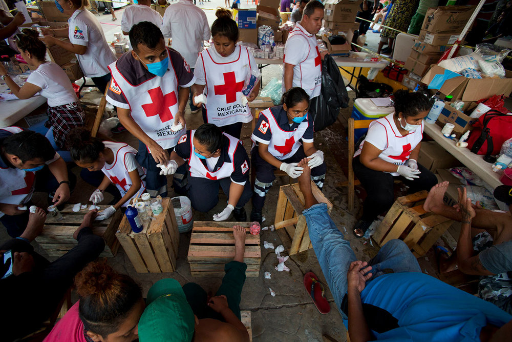 Volunteers from the Mexican Red Cross treat the blistered and cut feet of Central American migrants as a caravan of thousands stops for the night in Arriaga, Mexico, Friday, Oct. 26, 2018. (AP Photo/Rebecca Blackwell)