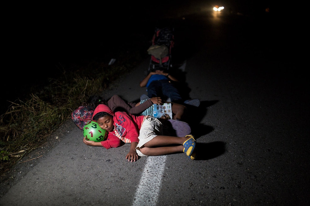 Jason, 11, sleeps using a toy ball as pillow during a break from walking early morning on the road that connects Pijijiapan with Arriaga, Mexico, on Oct. 26, 2018. (AP Photo/Rodrigo Abd)