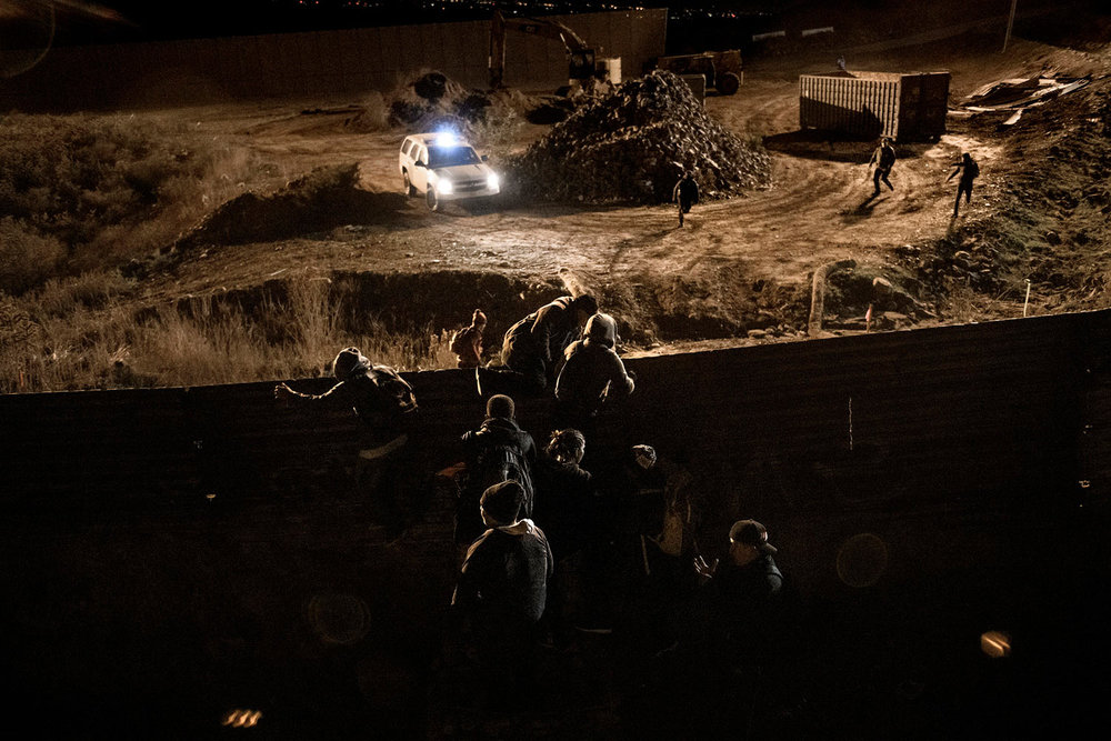 A border patrol officer is overpassed by migrants running while others already climbing the U.S. border fence jump inside the United States to San Diego, from Tijuana, Mexico, Tuesday, Dec. 25, 2018. (AP Photo/Daniel Ochoa de Olza)