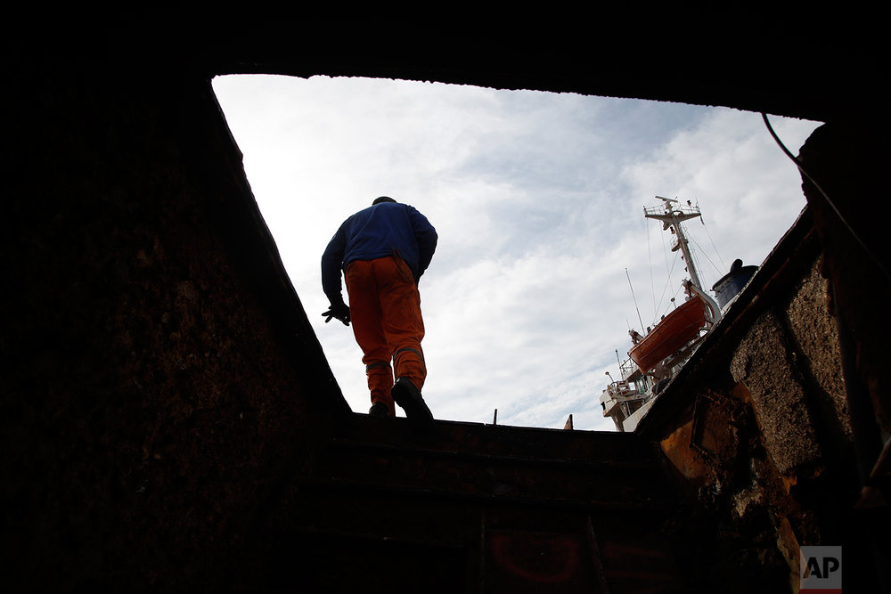 In this Monday, Nov. 5, 2018 photo, in a shipyard of Perama, west of Athens, a worker walks on a ferry that was recovered after spending years as a shipwreck. (AP Photo/Thanassis Stavrakis)
