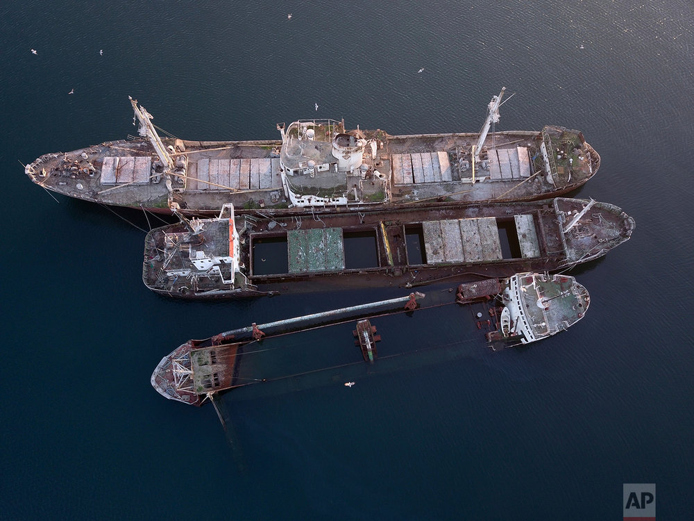 In this Friday, Dec. 4, 2018 photo, half sunken and abandoned ships are photographed in the Gulf of Elefsina, west of Athens. (AP Photo/Thanassis Stavrakis)