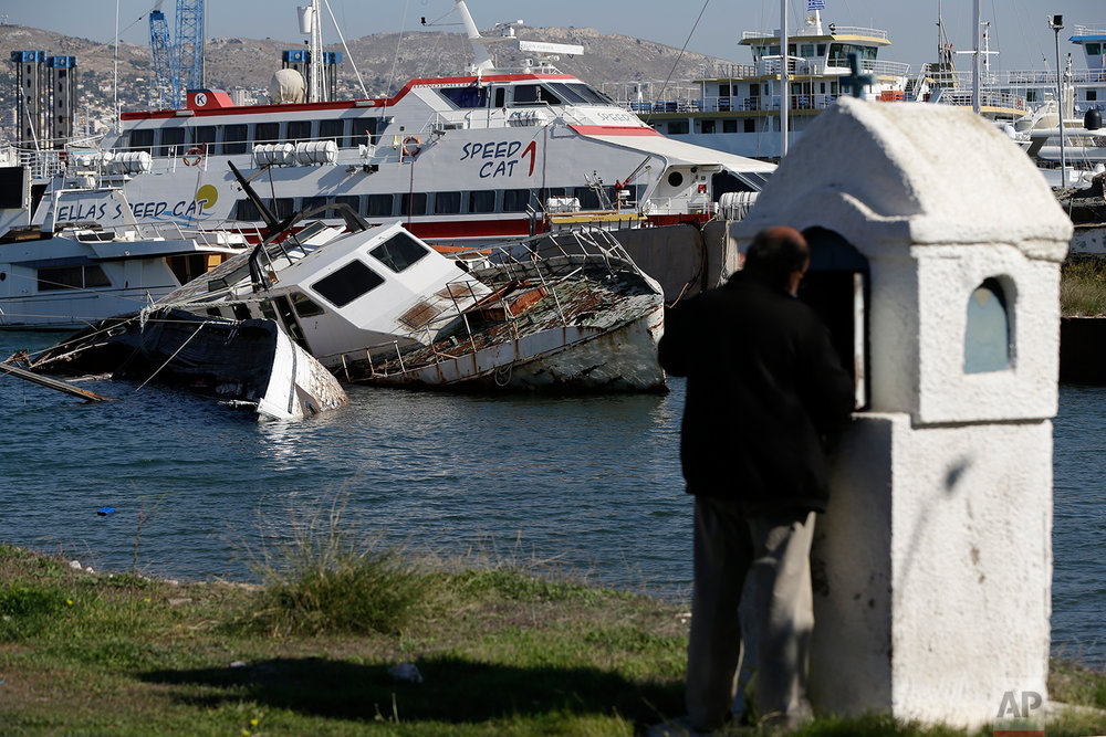 In this Tuesday, Nov. 6, 2018 photo, a half sunken small boat is photographed near a shipyard in Salamina island, west of Athens as a man lights a candle at a roadside shrine. (AP Photo/Thanassis Stavrakis)
